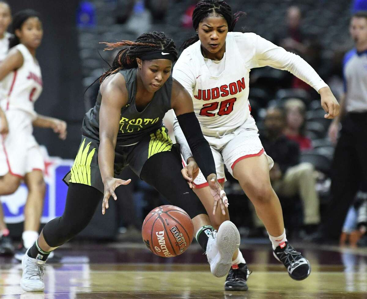 Michayla Gatewood of DeSoto, left, and Kierra Sanderlin (20) of Judson battle for a loose ball during the first-half of the Class 6A girls state championship game in the Alamodome on Saturday, March 2, 2019.