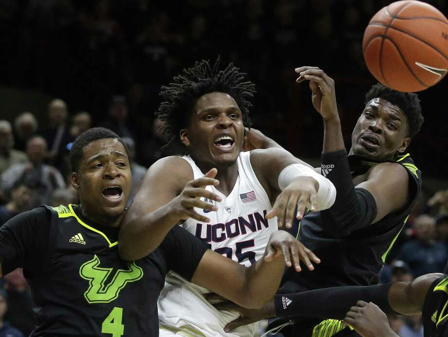 UConn's Josh Carlton, center, vies for the ball with with a pair of USF players earlier this season. Photo: Steven Senne / Associated Press / Copyright 2019 The Associated Press. All rights reserved