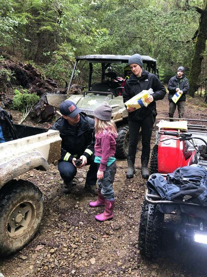 A member of the search and rescue team talks to one of the Carrico sisters after they were found 1.4 miles south of their home on Sunday morning after being missing since Friday afternoon.  Photo: Courtesy Of Humboldt County Sheriff's Office