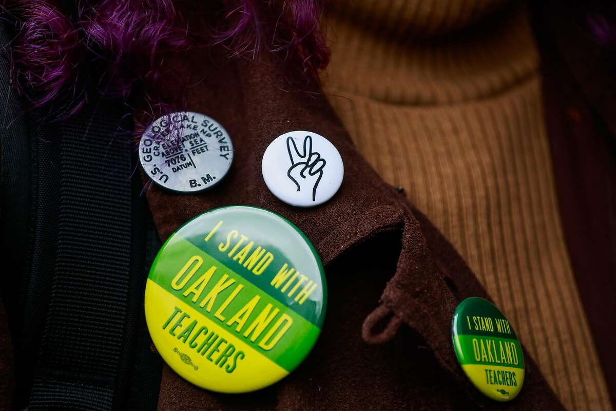A teacher shows off her pins as she lines up with other teachers to vote on whether or not to ratify a tentative contract that the Oakland Education Association and Oakland Unified School District proposed in Oakland, California, on Sunday, March 3, 2019.