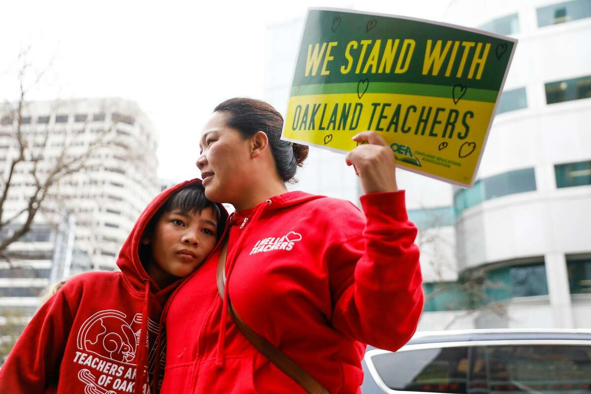 Lisa Sutton (right) embraced her son Hudson Sutton, 12 (left) as they came out to show support for teachers outside the Paramount Theater in Oakland, California, on Sunday, March 3, 2019. Teachers lined up to vote on whether or not to ratify a tentative contract that the Oakland Education Association and Oakland Unified School District.