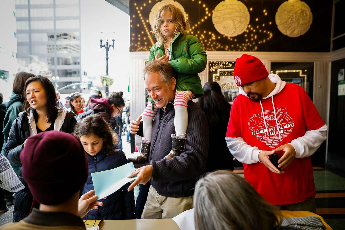 Teacher Moss Hahn (center) and his daughters Sasha Hahn (left) and Hailey Hahn (right) check in before voting on whether or not to ratify a tentative contract that the Oakland Education Association and Oakland Unified School District proposed in Oakland, California, on Sunday, March 3, 2019.