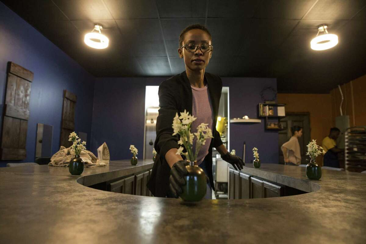 Indigo hostess Jessica Kitomary sets up flowers around a 13-seat horseshoe-shaped bar that gives diners a front-row seat to the kitchen of chef Jonathan Rhodes.