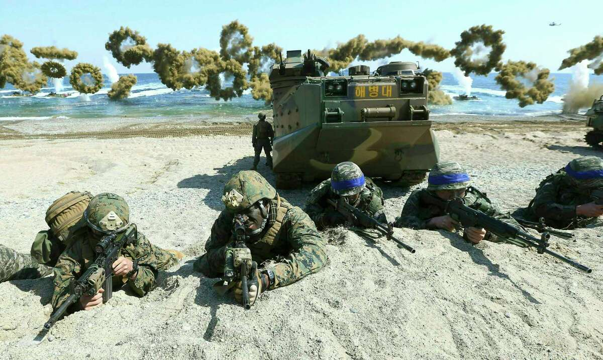 FILE - In this March 12, 2016, file photo, Marines of the U.S., left, and South Korea, wearing blue headbands on their helmets, take positions after landing on a beach during the joint military combined amphibious exercise, called Ssangyong, part of the Key Resolve and Foal Eagle military exercises, in Pohang, South Korea. South Korea and the U.S. say they've decided to end their springtime military drills to back diplomacy with North Korea. (Kim Jun-bum/Yonhap via AP, File)