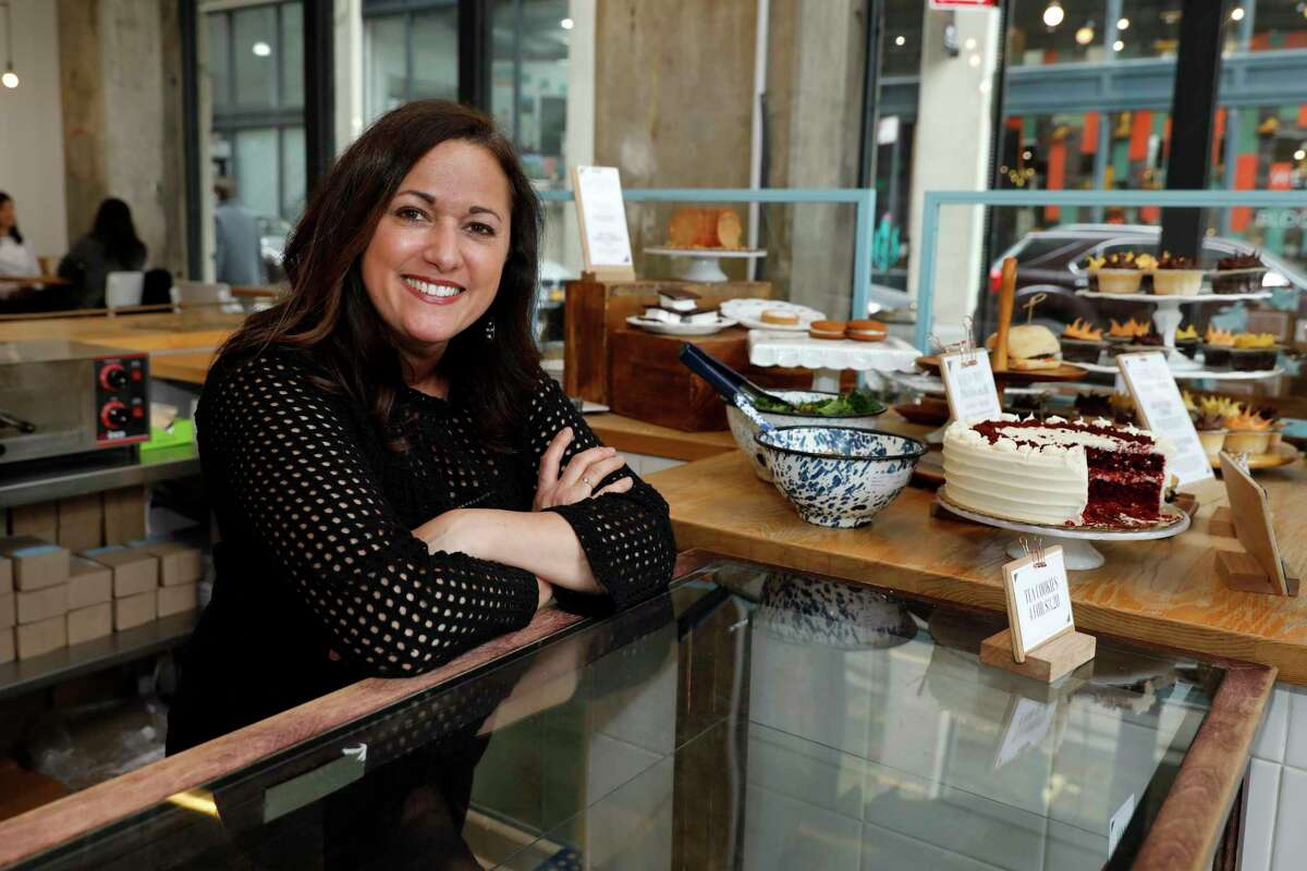 """In this Wednesday, Feb. 6, 2019 photo, Dawn Casale, founder of One Girl Cookies, poses for photos in her shop in the Dumbo neighborhood of the Brooklyn borough of New York. Mayor Bill de Blasio wants New York to become the first place in the 50 states to make private businesses provide time off with pay. Employees at Casale's bakery get paid time off after five years, or if they're managers; others can arrange unpaid vacation, she said. """"I would love to be able to provide vacation time to my employees ... but the reality of it is not whether or not we want to give it ?- it's whether we can give it,"""" said Casale. (AP Photo/Richard Drew)"""