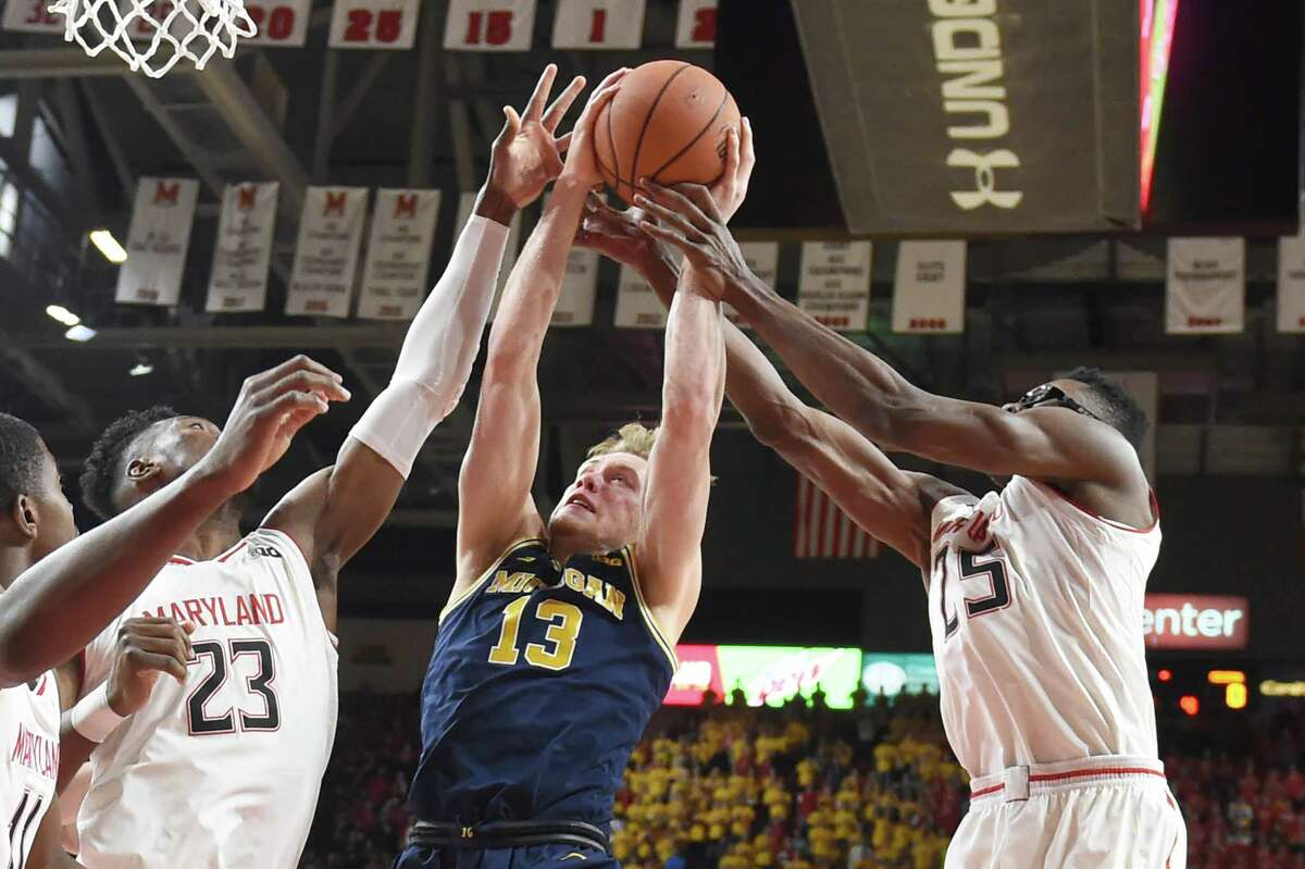 COLLEGE PARK, MD - MARCH 03: Ignas Brazdeikis #13 of the Michigan Wolverines pulls down a rebound between Bruno Fernando #23 and Jalen Smith #25 of the Maryland Terrapins second half during a college basketball game at the XFinity Center on March 3, 2019 in College Park, Maryland. (Photo by Mitchell Layton/Getty Images)