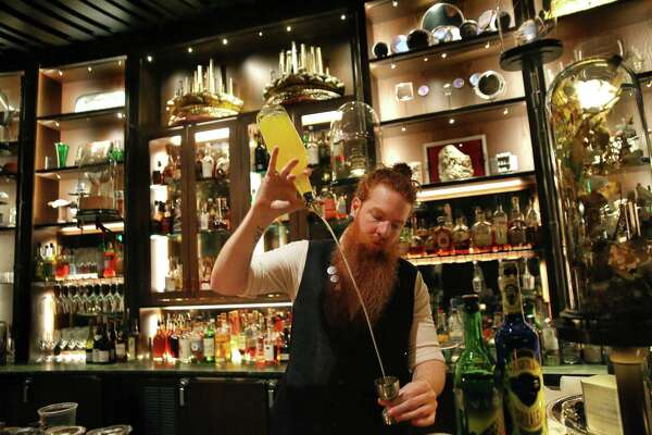 Bartender Craig Rovensky makes a Phoenix Nest at Renee Erickson's new restaurant and bar Deep Dive in the Amazon Spheres, Thursday, Feb. 28, 2019. Erickson opened Deep Dive, and Italian restaurant Willmott's Ghost, in the Spheres a few months ago and it is already a bustling, hotspot for the Amazon crowd. Deep Dive has a dark and intriguing atmosphere and a menu that features a swath of fancy cocktails and a Salmon roe-topped $18 hotdog.
