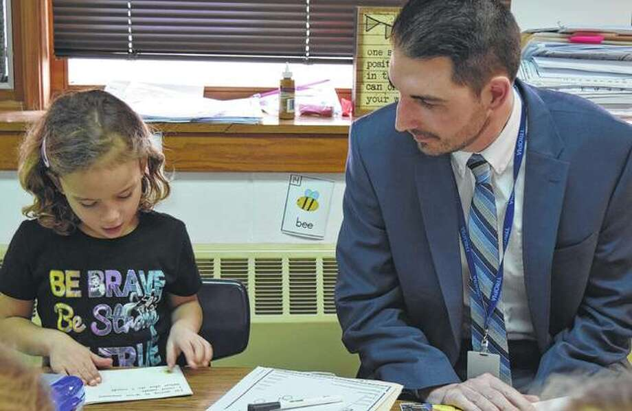 Triopia High School Principal Adam Dean helps kindergartner Journey Staake with reading. Photo: Samantha McDaniel-Ogletree   Journal-Courier