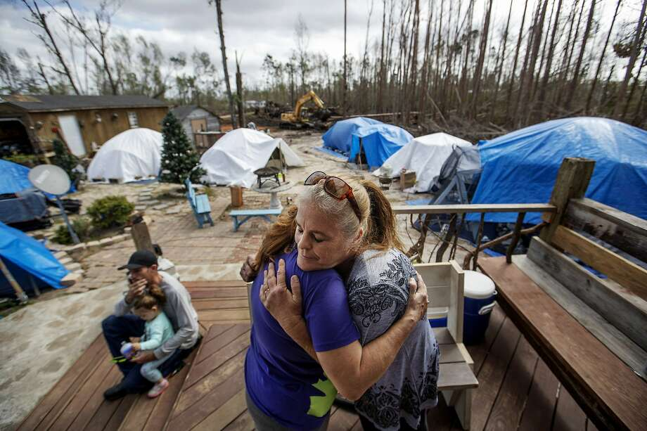 """Diahnn """"Shelly"""" Summers (right) embraces Lori Hogan Jan. 23. Hogan is living in a tent in Summers' yard in Youngstown, Fla. Photo: David Goldman / Associated Press"""