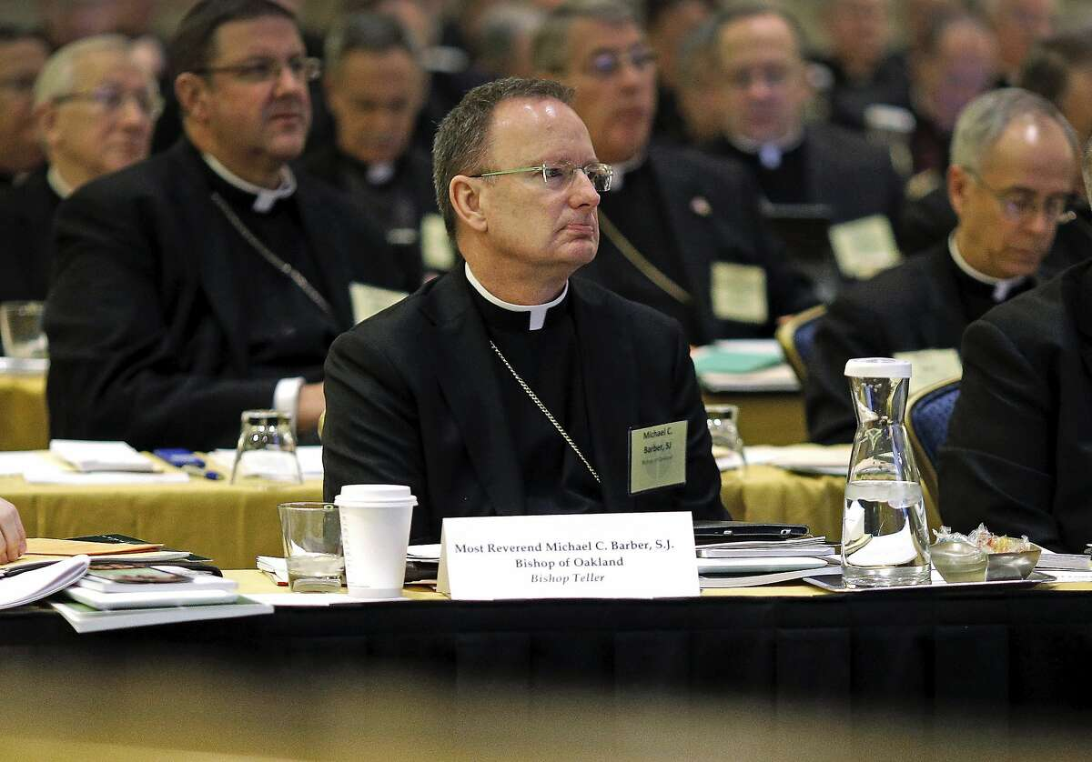 """FILE - In this Nov. 12, 2013, file photo, Roman Catholic Diocese of Oakland Bishop Michael Barber, center, listens to a presentation alongside fellow bishops at the United States Conference of Catholic Bishops' annual fall meeting in Baltimore. The Catholic Diocese of Oakland, Calif., has released the names of 45 priests, deacons and religious brothers who officials say are """"credibly accused"""" of sexually abusing minors. The San Francisco Chronicle says Monday that Oakland's list goes back to 1962, when the diocese was founded. None of the men are currently in the ministry. Of the 45 people named, 20 were priests. (AP Photo/Patrick Semansky, File)"""