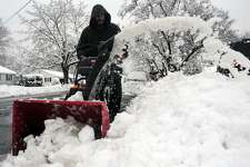 Juan Flores uses a snow blower to clean up Monday morning after snow fell in Stratford, Conn. March 4, 2019.