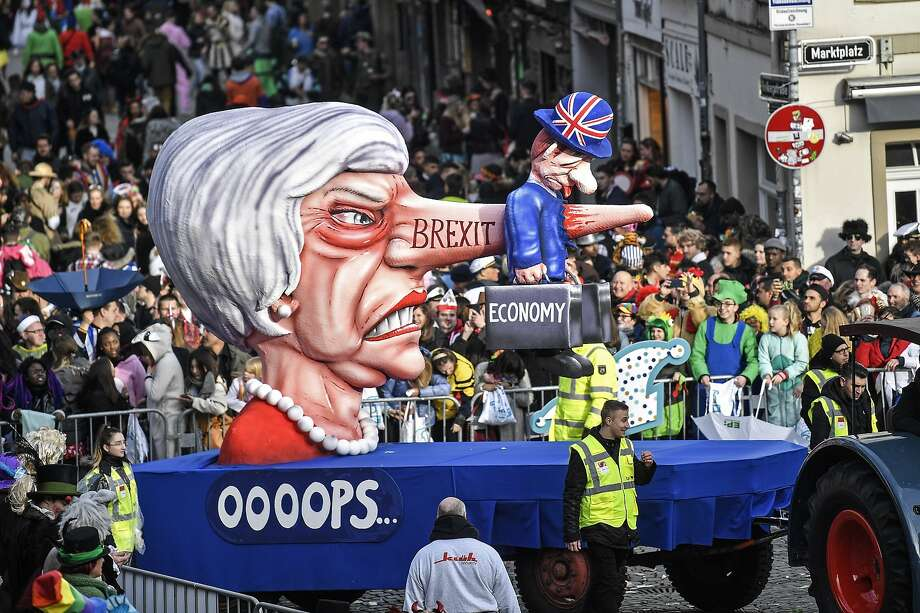 """A float at a Carnival street parade in Duesseldorf, Germany, depicts Prime Minister Theresa May with a Pinocchio nose labeled """"Brexit"""" skewering the British economy. Photo: Martin Meissner / Associated Press"""