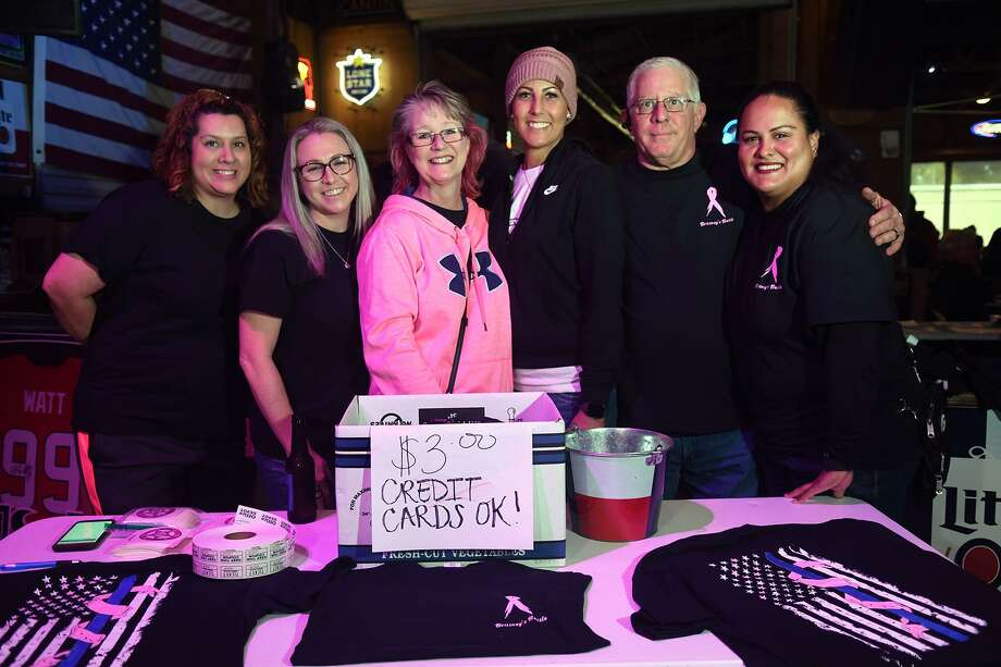 Precinct 4 Constable's Deputy Brittney Buchkar, center, who is battling breast cancer, poses for a photo with friend Eda Brooks, from left, fellow Pct. 4 deputy Liz Garcia, mom Stephanie Martino, dad Joe Martino, a Pct. 4 deputy, and Pct. 4 deputy Toni Rebeles during a fundraiserfor for Buchkar at Bareback Bar and Icehouse in Spring on March 3, 2019. Photo: Jerry Baker, Houston Chronicle / Contributor / Houston Chronicle