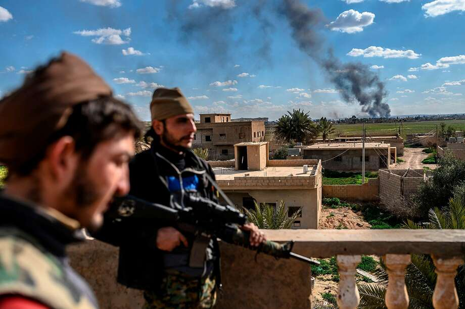 Syrian Democratic Forces members take position on a rooftop during shelling Sunday of Islamic State militants in Baghouz. Photo: Bulent Kilic / AFP / Getty Images
