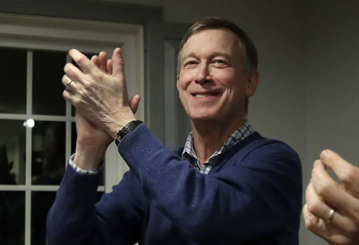 FILE - In this Feb. 13, 2019, file photo, former Colorado Gov. John Hickenlooper, left, applauds at a campaign house party, in Manchester, N.H. Hickenlooper is running for president, becoming the second governor to jump into the sprawling Democratic 2020 contest. Hickenlooper is a former brewpub owner and Denver mayor who hopes his two terms governing a swing state shows that he can unite the country. (AP Photo/Elise Amendola, File)