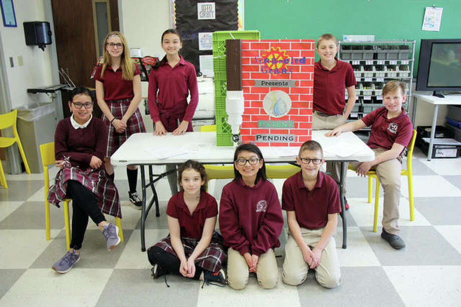 Scrambled Gears members, front row from left, Edna Conness, Juan-Manuel Callis and Garrett Harbison. Back row, Sophia Windorff, Hannah Harrison, Reanna Compton, Tristan Luehmann and Lincoln Duffy. The group poses Friday with their invented device, the WaterSpark. The team, based at St. John Neumann Catholic School in Maryville, filed a patent for the device Thursday. Not pictured is teammate Samantha Fulton. Photo: Charles Bolinger | The Intelligencer