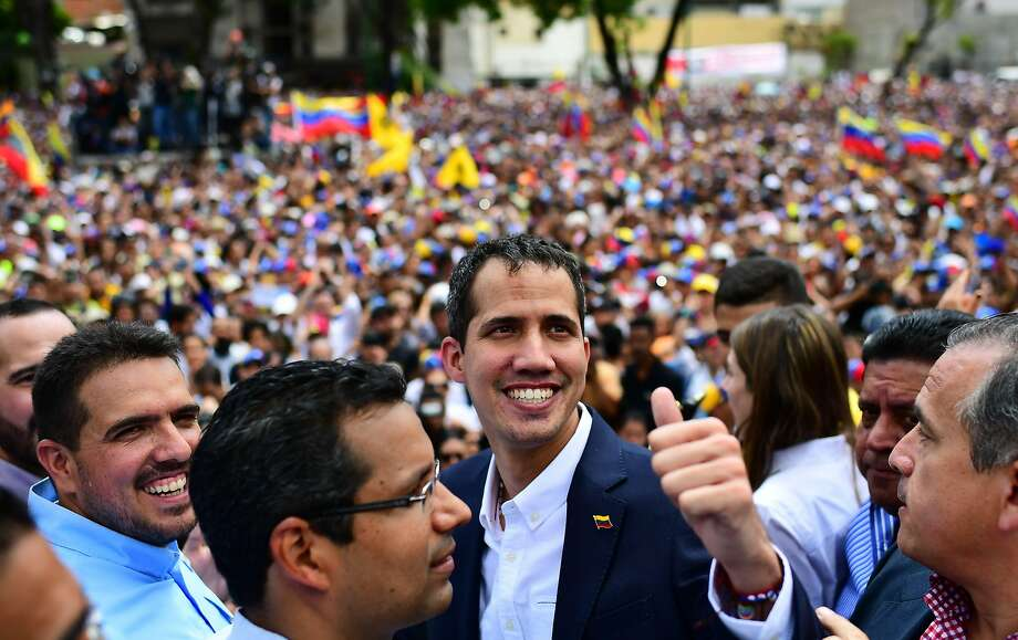 Opposition leader Juan Guaidó greets supporters upon his arrival in Caracas. He had defied a travel ban and left Venezuela to visit neighboring nations. Photo: Ronaldo Schemidt / AFP / Getty Images