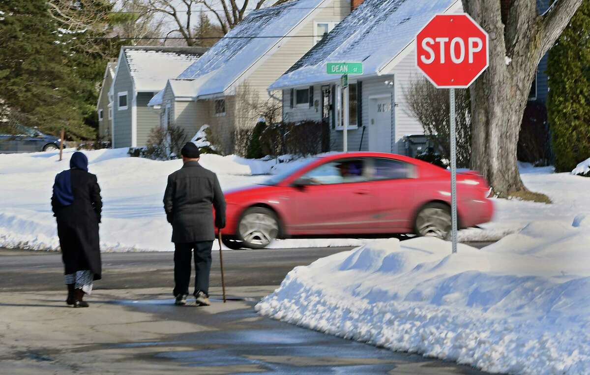 A car is seen coming down Dean St. as a couple takes a walk on Monday, March 4, 2019 in Niskayuna, N.Y. (Lori Van Buren/Times Union)