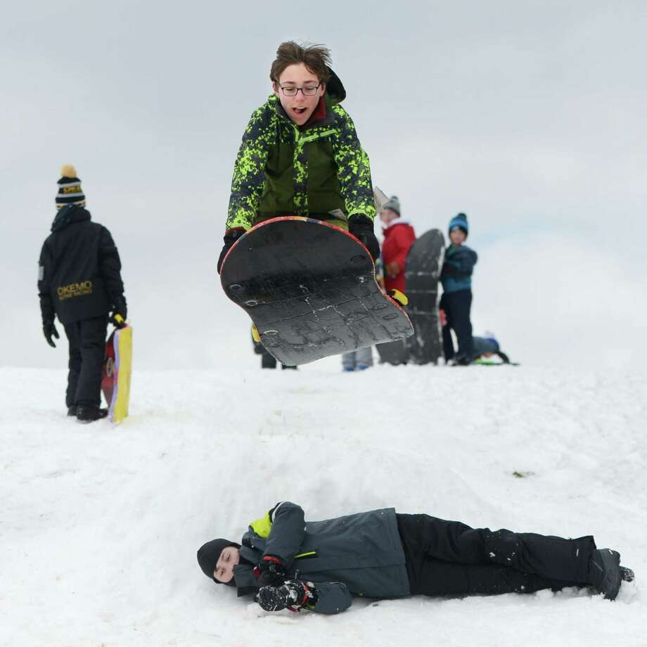 Reed Kemp, 14, ramps his sled over a friend at Innis Arden Golf Club in Old Greenwich, Conn. Monday, March 4, 2019. Greenwich received eight inches of snow that caused school to be cancelled for the first time in the 2018-2019 year. Photo: Tyler Sizemore / Hearst Connecticut Media / Greenwich Time