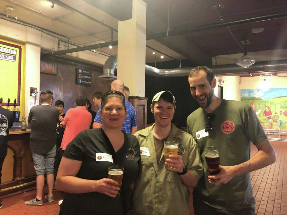 Foam Rangers Homebrew Club members Ryann Brzoska (pictured left), Steven Distelhorst and Jon Jarvis smile as they drink beer at the 15th annual Houston rally hosted by the American Homebrewers Association. The event was held on Saturday, Feb. 23, at Saint Arnold Brewing Company. Photo: Tracy Maness