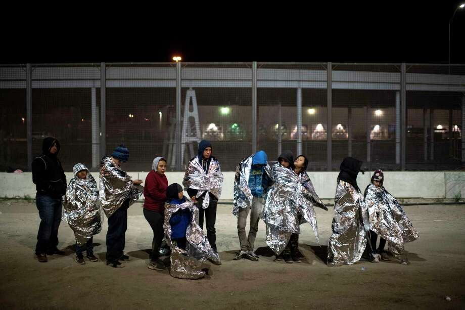Migrant families wrapped in mylar blankets stand in line waiting to be loaded into a Border Patrol transport van to take them to a nearby holding facility in El Paso, Texas on Feb. 22, 2019. Photo: Washington Post Photo By Carolyn Van Houten / The Washington Post