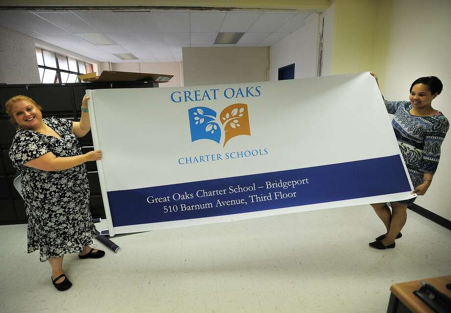 Then executive director/principal Monica Maccera Filppu, left and Superintendent of Great Oaks Foundation Christina Grant unveil the banner for the new Great Oaks Charter School at 510 Barnum Avenue in Bridgeport, Conn. on Thursday, August 21, 2014. Photo: Brian A. Pounds / Brian A. Pounds / Connecticut Post