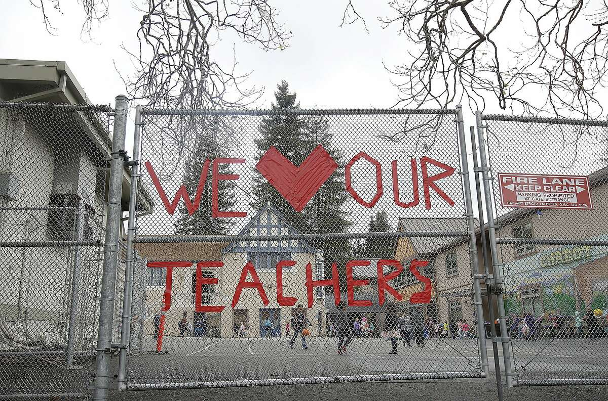 A sign supporting teachers is shown on a fence outside of Chabot Elementary School in Oakland, Calif., Monday, March 4, 2019. Thousands of Oakland teachers are back in classrooms after union members voted to approve a contract deal. (AP Photo/Jeff Chiu)