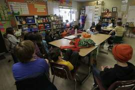 Chabot Elementary School fourth grade teacher Laura Shield, top rear, listens to students in her class in Oakland, Calif., Monday, March 4, 2019. Thousands of Oakland teachers are back in classrooms after union members voted to approve a contract deal. (AP Photo/Jeff Chiu)