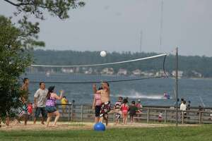 A group of friends play a game of beach volleyball in this file photo at Lake Conroe Park in Conroe.