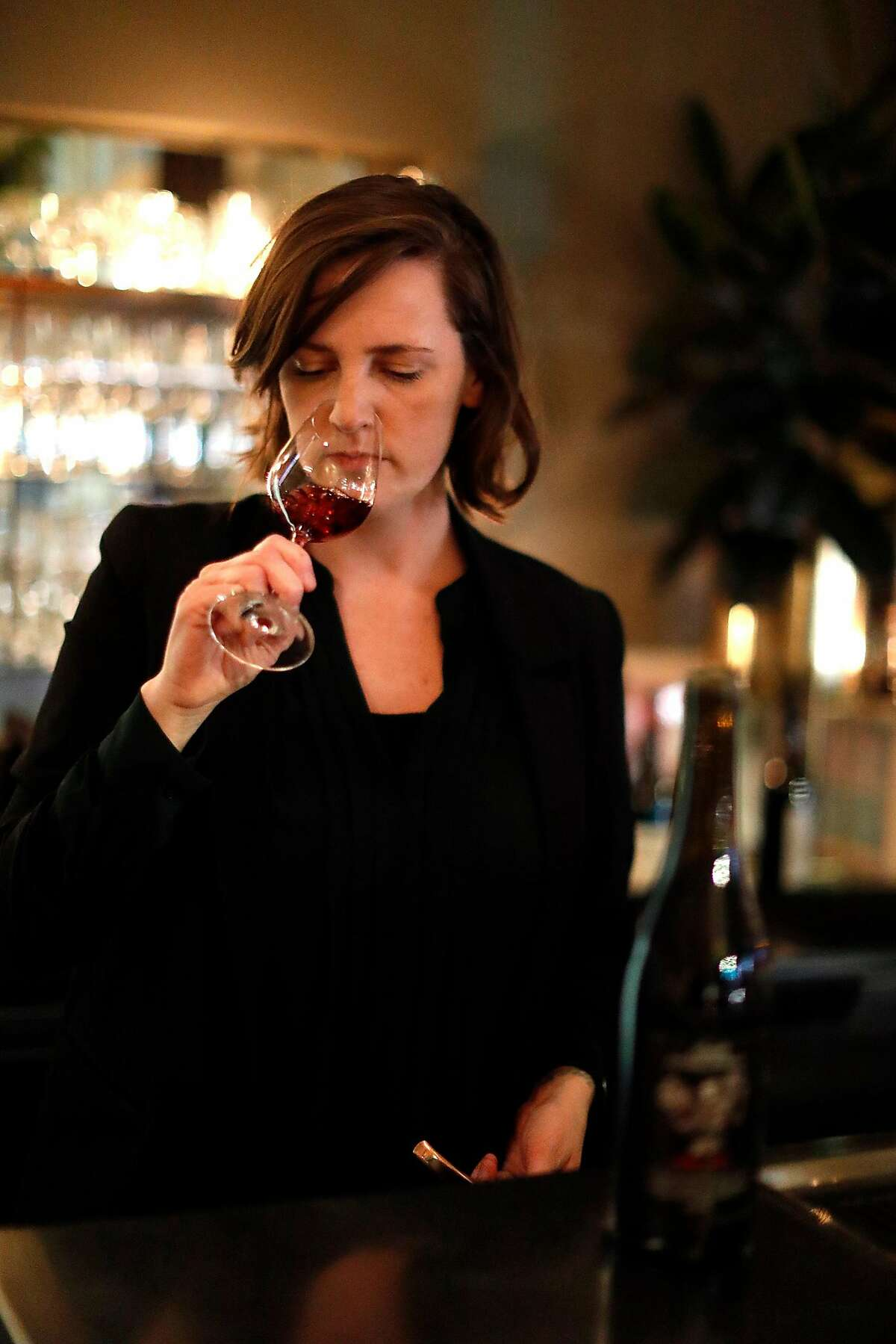 Louisa Smith, Lord Stanley wine director, checks the aroma of a glass of wine at the restaurant in San Francisco, Calif., on Wednesday, February 20, 2019.