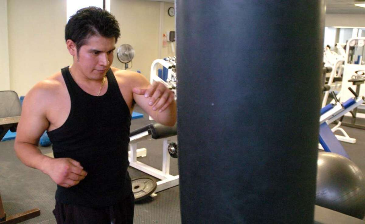 Milton Zhina, 26, of Danbury, works out on the heavy bag at the War Memorial in Danbury, July 23, 2010.