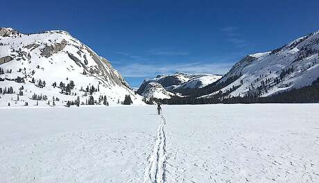 Laura Pilewski cross-county skis across Tenaya Lake in the snow-bound wilds of Yosemite National Park