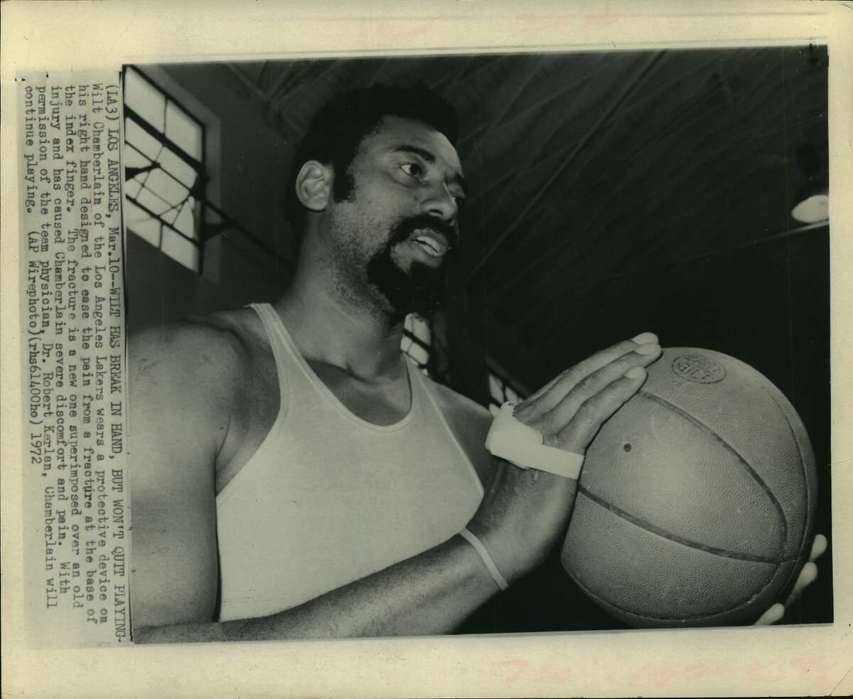 Wilt has break in hand, but won't quit playing--Wilt chamberlain of the Los Angeles Lakers wears a protective device on his right hand designed to ease the pain from a fracture at the base of the index finger. The fracture is a new one superimposed over an old injury and has caused Chamberlain severe discomfort and pain. With permission of the team physician, Dr. Robert Kerlan, Chamberlain will continue playing.