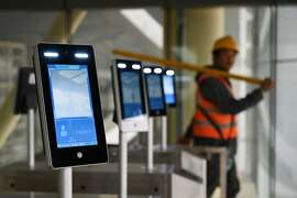 A construction worker walks past facial recognition screens at the entrance to the terminal building of the new Beijing Daxing International Airport, in Beijing on March 1, 2019. - Claimed to be the largest single airport terminal in the world, and aimed at easing the passenger load of Beijing's other two airports, the new airport is scheduled to be completed in June 2019, and begin operations in September 2019. (Photo by GREG BAKER / AFP)GREG BAKER/AFP/Getty Images