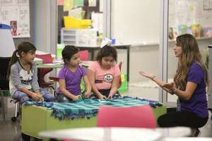 Third-grade teacher Sara Cox speaks to 8-year-old Camilla Marquez, left, and 6-year-old Mariah Torrez, center, and 8-year-old Amerie Muniz, as they cut tassels into a blanket at Buice Elementary in Odessa on Nov. 29. The blankets were donated to the Humane Society of Odessa.
