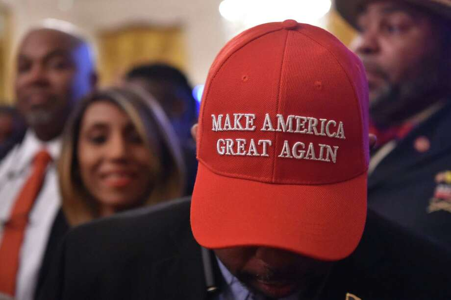 "A man wearing a ""Make American Great Again"" (MAGA) cap awaits the start of a White House reception in honor of National African American History Month hosted by President Donald Trump and the First Lady. A reader asks what the MAGA statement really means. Photo: NICHOLAS KAMM /AFP /Getty Images / AFP or licensors"