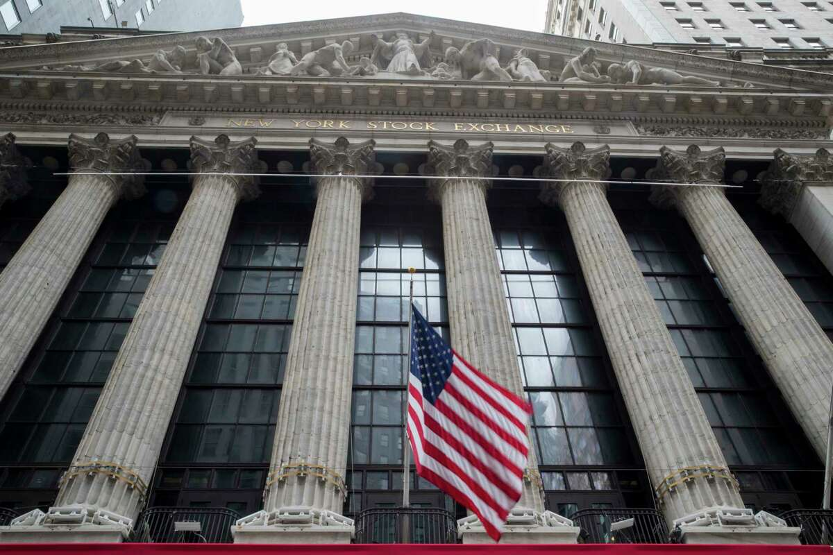 FILE- In this Nov. 20, 2018, file photo an American flag flies outside New York Stock Exchange. Stocks are opening broadly higher on Wall Street following reports that the U.S. and China are getting closer to a deal on trade. Technology stocks, industrial and internet companies were among the biggest gainers in early trading Monday, March 4, 2019. (AP Photo/Mary Altaffer, File)