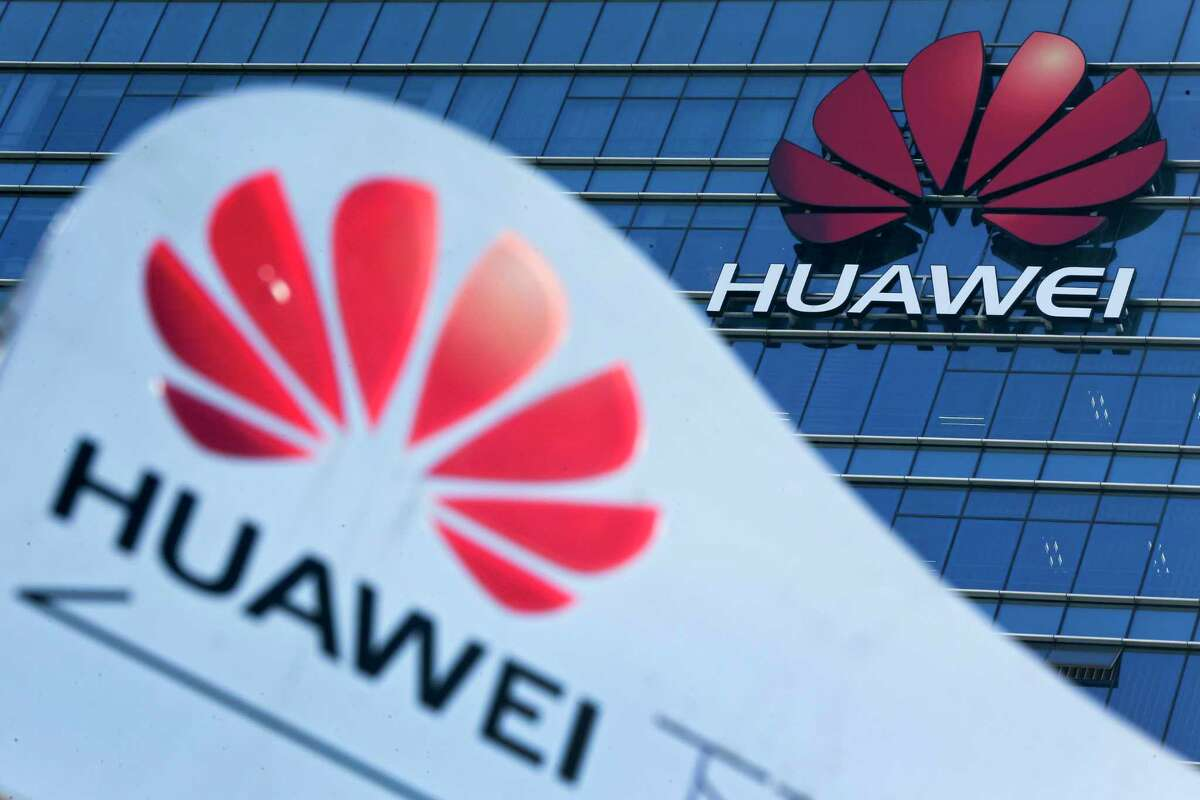 FILE - This Dec. 18, 2018, file photo, shows company signage on display near the Huawei office building at its research and development center in Dongguan, in south China's Guangdong province. China says the U.S. is using a double standard in claiming Chinese law requires telecoms giant Huawei to violate other countries' information security. (AP Photo/Andy Wong, File)