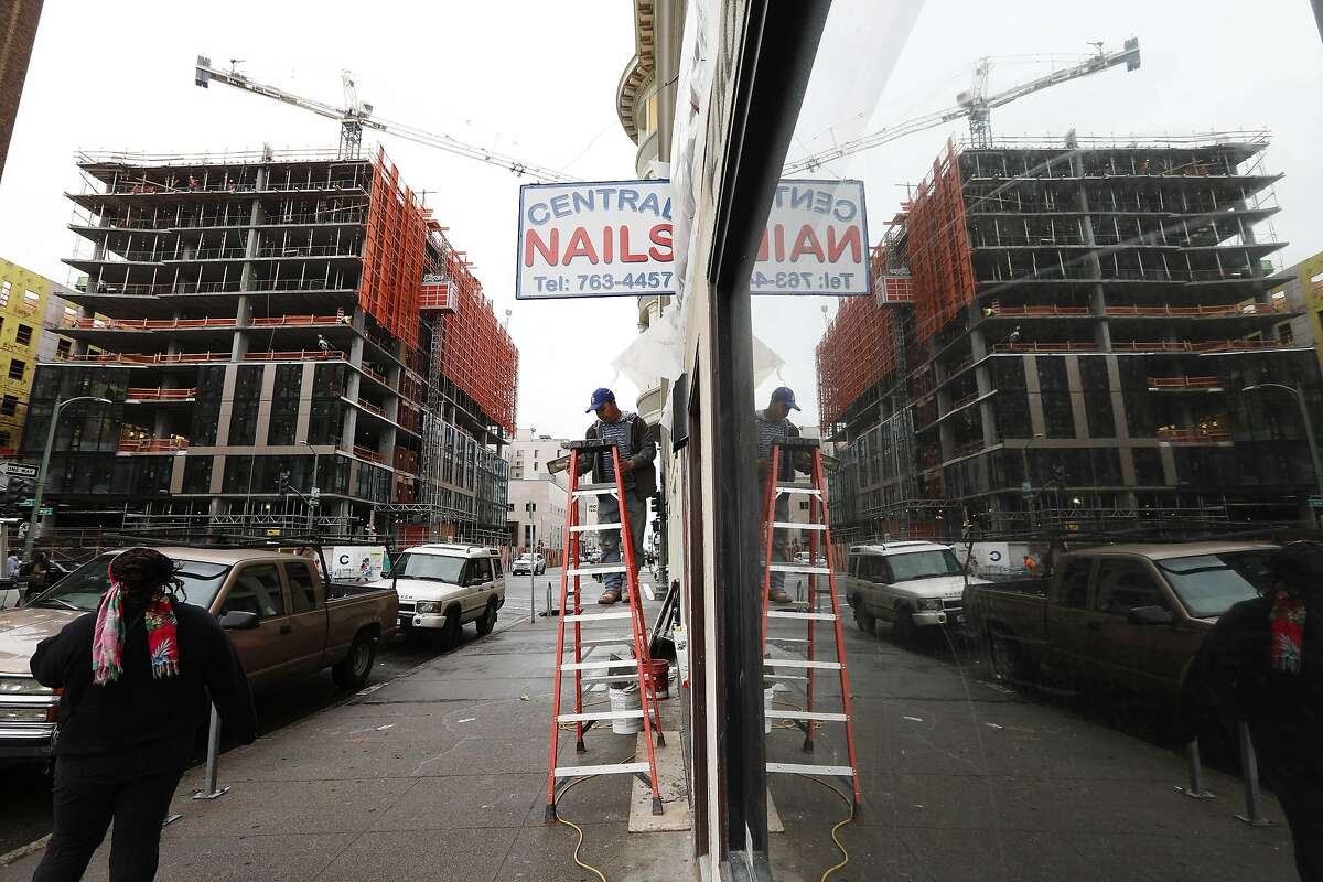A new building is seen under construction on Franklin Street at 14th Street and refelcted in a store front window on Franklin Street on Monday, March 4, 2019 in Oakland, Calif.