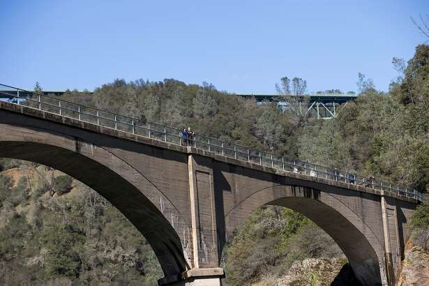 """Hikers walk along the historic Mountain Quarries Railroad Bridge, popularly known as """"No Hands Bridge,"""" in Auburn, Calif., on Monday, February 18, 2019. The bridge is located along the Black Hole of Calcutta Falls trail and makes a great vista for photographs."""