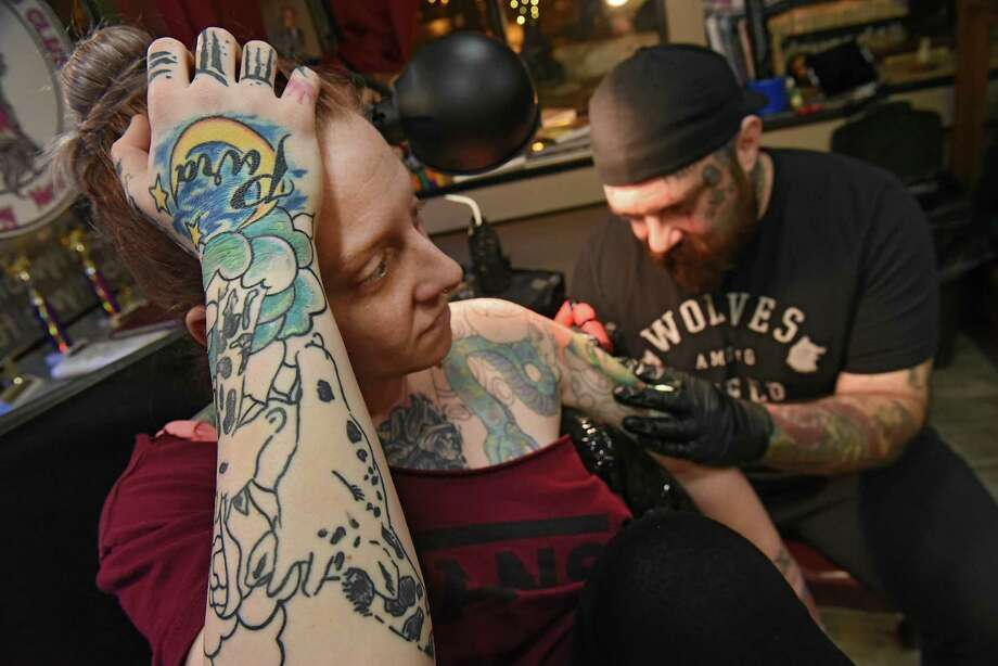 Shop owner Ian Macintyre works on client Janin Penman of Albany at The Curly Wolf Tattoo Club on Wednesday, Feb. 6, 2019 in Albany, N.Y. In New York, you have to be 18 to legally get a tattoo. (Lori Van Buren/Times Union Photo: Lori Van Buren / 40046125A