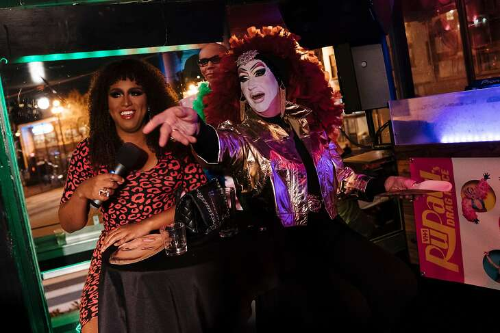"""Honey Mahogany and Sister Roma throw out Miley Cyrus face masks during the """"RuPaul's Drag Race"""" Season 11 premiere party at the The Lookout in San Francisco, Calif., on Thursday, Feb. 28, 2019."""