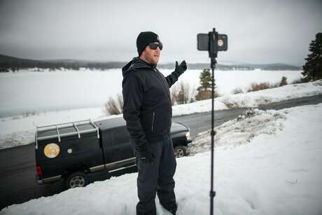 Bryan Allegretto takes a video on his phone for audiences on YouTube and Instagram to explain the day's snow forecast at Boca Reservoir (Nevada County). Photo: AJ Marino / Special To The Chronicle