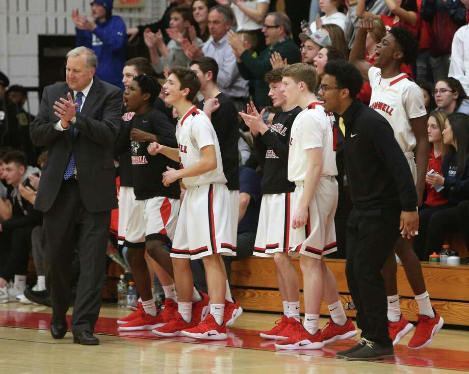 Cromwell High School's boys varsity basketball team members and Head Coach John Pinone celebrate a shot on the court during the game against Old Lyme High School in Cromwell on Monday, Feb. 18. Photo: Emily J. Reynolds / For Hearst Connecticut Media / Connecticut Post Freelance