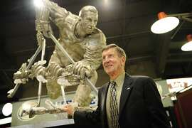 "This photo taken Oc. 18, 2008, shows former Detroit Red Wing Ted Lindsay posing with a statue erected in his honor at Joe Louis Arena, in Detroit.  Lindsay lived to do what he thought was right. He pioneered the first NHL players' union, started the tradition of taking the Stanley Cup closer to fans in the stands and refused to attend his own Hall of Fame induction ceremony because only men were allowed. Lindsay, who provided muscle and meanness on the Detroit Red Wings' famed ""Production Line"" of the 1950s, died Monday, March 4, 2019. He was 93. (David Guralnick/Detroit News via AP)"