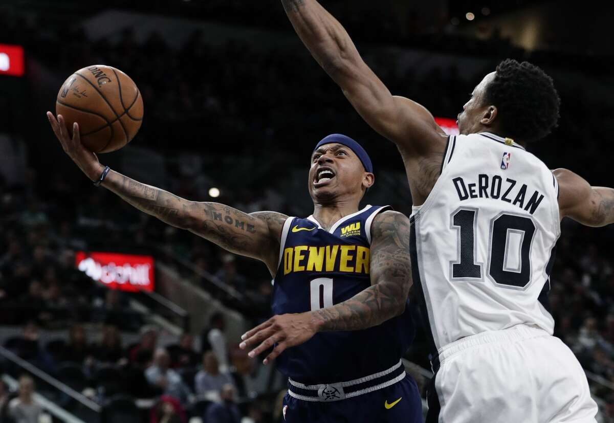 Denver Nuggets guard Isaiah Thomas (0) scores past San Antonio Spurs guard DeMar DeRozan (10) during the first half of an NBA basketball game, in San Antonio, Monday, March 4, 2019. (AP Photo/Eric Gay)