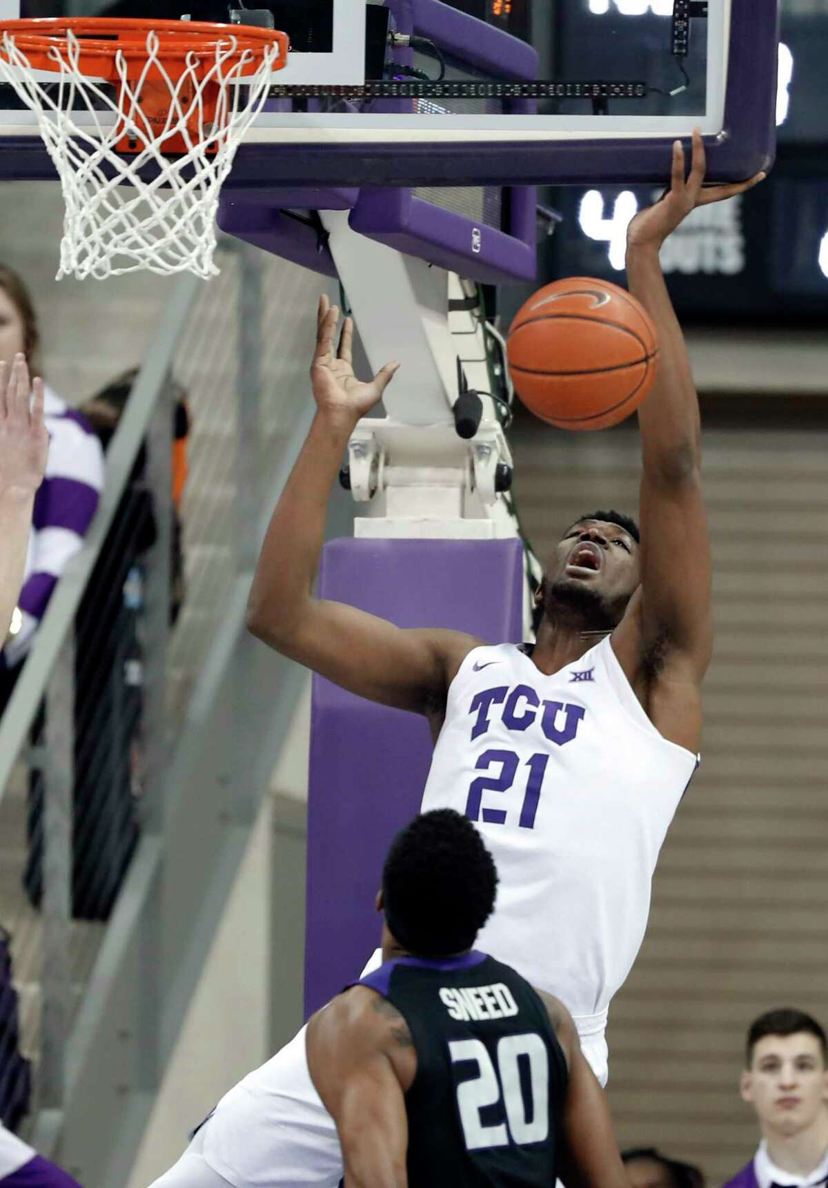 TCU center Kevin Samuel (21) loses control of the ball while shooting against Kansas State forward Xavier Sneed (20) in the first half of an NCAA college basketball game in Fort Worth, Texas, Monday, March 4, 2019.