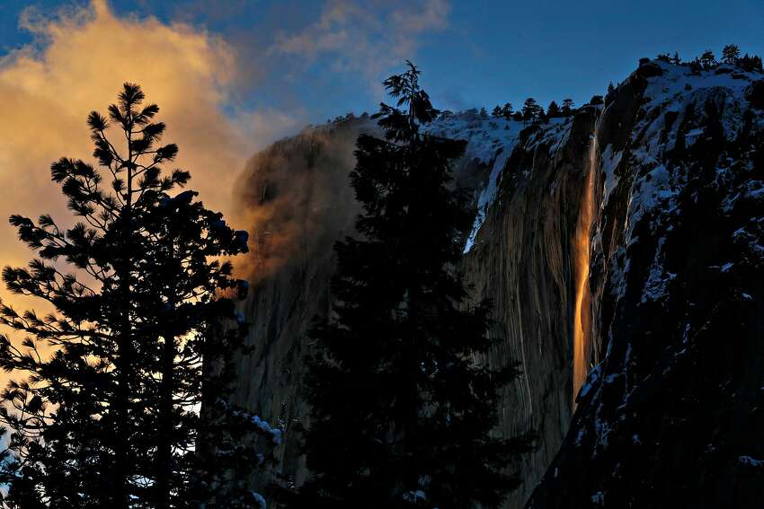 FILE - Horsetail Falls lights up from the setting sun against El Capitan in Yosemite National Park in Yosemite, Calif., on Monday, February 18, 2019. A 10-year-old girl from Colorado has just become the youngest person to reach the rock formation's summit.