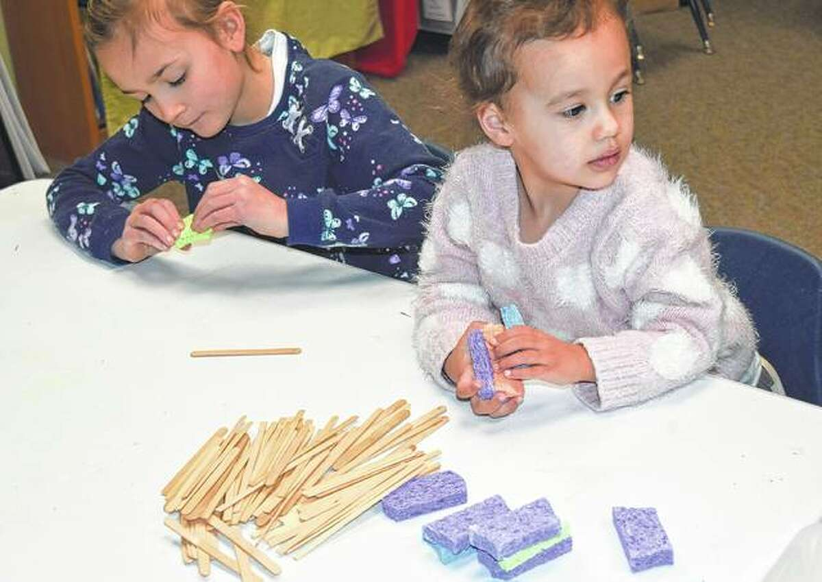 Eleanor Mack (left), 6, and Vivian Mack, 2, the daughters of Brette and Keenan Mack of Jacksonville, prepare to build towers Monday at the Jacksonville Public Library as part of its Little Learners program.
