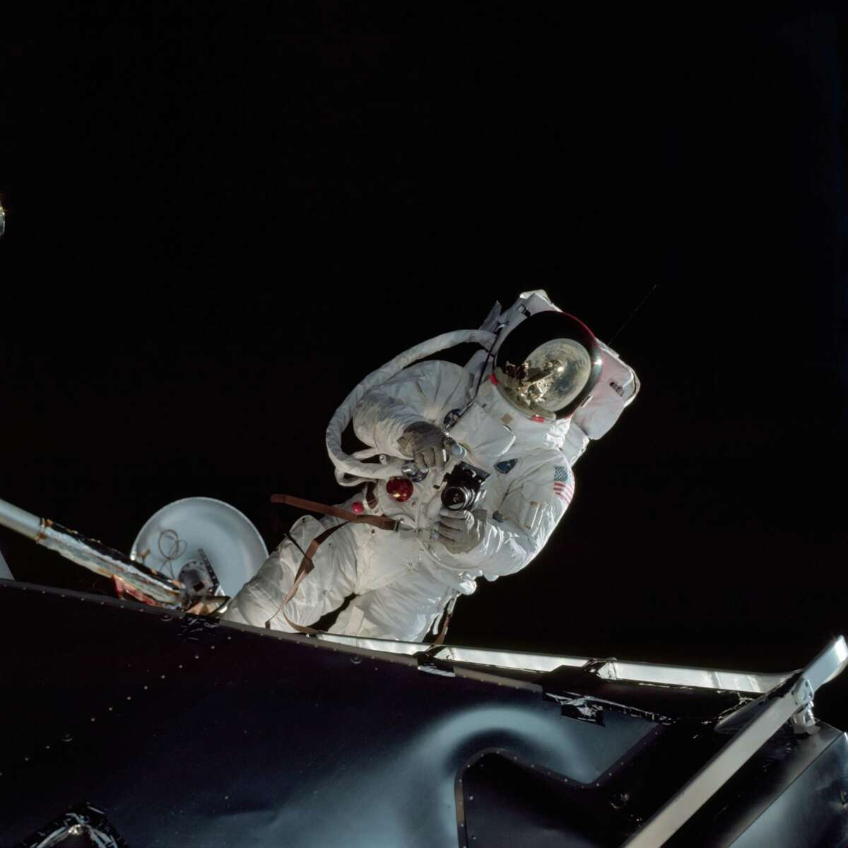 Astronaut Russell L. Schweickart operates a 70mm Hasselblad camera during his extravehicular activity on the fourth day of the Apollo 9 mission. The Command/Service Module and the Lunar Module 3